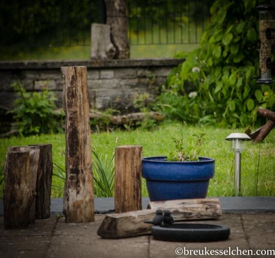 Holzscheiten um die Blumenkübel herum lenken vom Blick des Bodens ab.